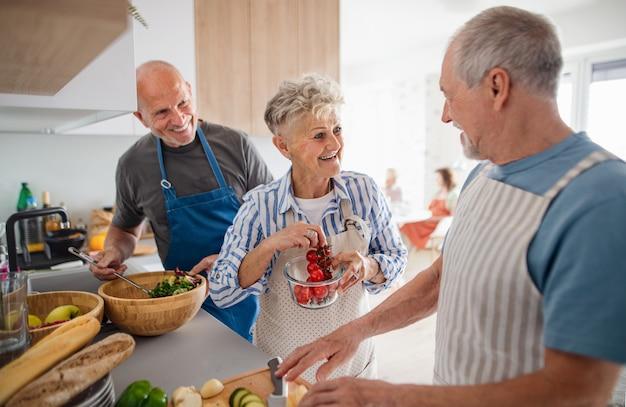 Grupo de amigos sênior, festejando dentro de casa, cozinhando e conversando.