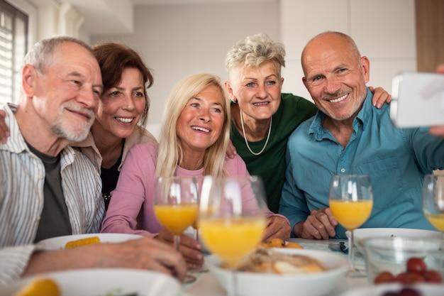 Grupo de amigos sênior, festejando dentro de casa, tomando selfie ao comer na mesa.