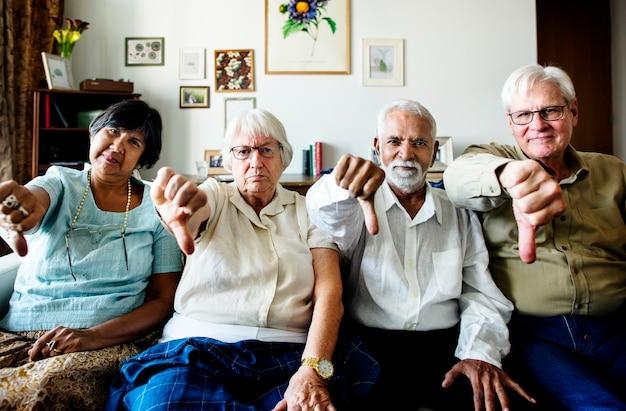 Grupo de amigos seniores gesticulando polegares para baixo sinal