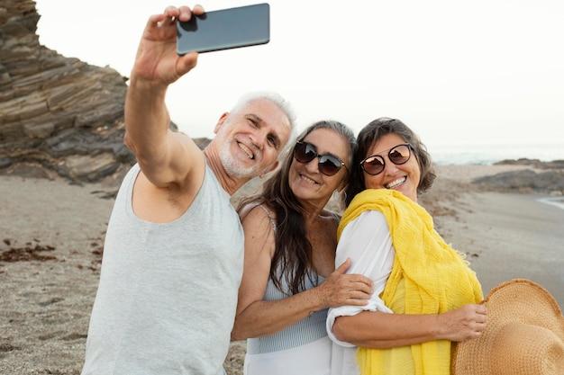 Grupo de amigos seniores tirando selfie com smartphone na praia