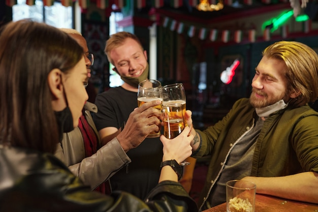 Grupo de amigos sentado à mesa brindando com cerveja no bar