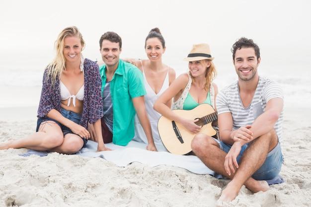 Grupo de amigos sentado na praia com guitarra