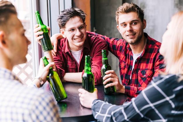 Grupo de amigos sentados ao redor da mesa, apreciando a bebida no restaurante pub