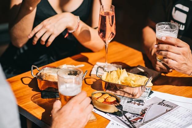Grupo de amigos sentados em um terraço de verão com cerveja e champanhe nas mãos e petiscos na mesa