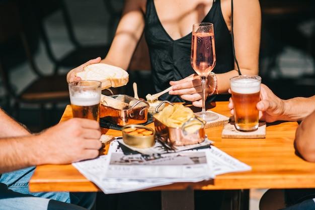 Grupo de amigos sentados em um terraço de verão com cerveja e vinho nas mãos e petiscos na mesa
