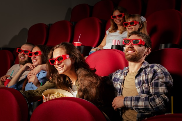 Grupo de amigos sentados no cinema com pipoca e bebidas
