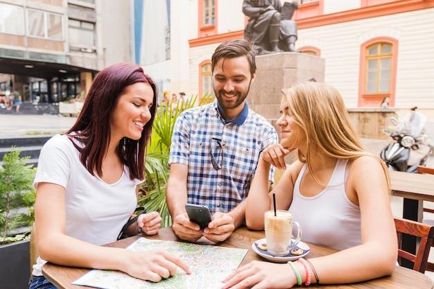 Grupo de amigos sentados no restaurante à procura de direção no smartphone