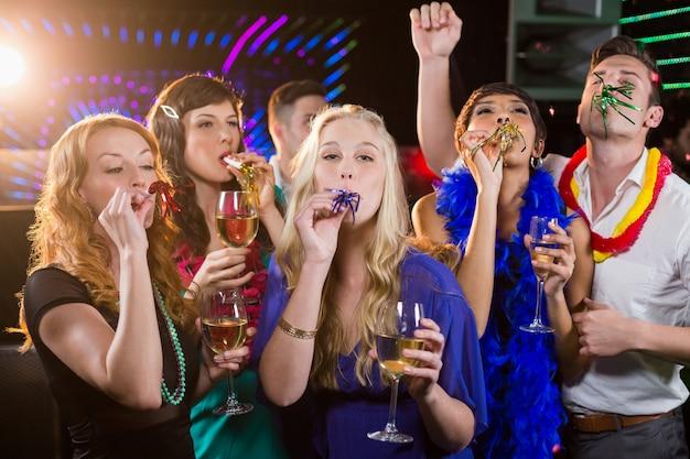 Grupo de amigos soprando buzina de festa no bar