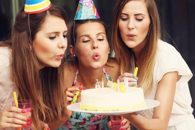 Grupo de amigos soprando velas em um bolo de aniversário