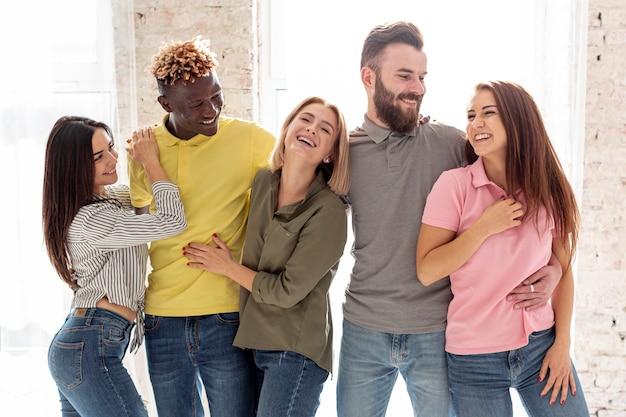 Grupo de amigos sorridentes, abraçando uns aos outros