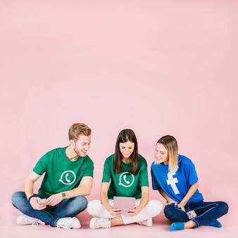 Grupo de amigos sorridentes, olhando para tablet digital