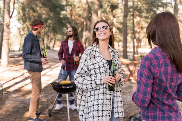 Grupo de amigos sorridentes tomando cerveja no churrasco