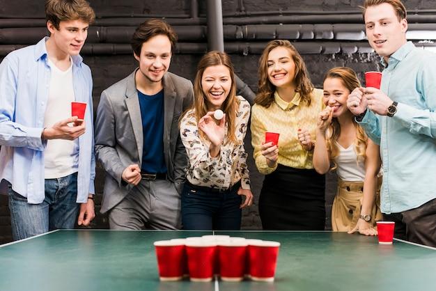 Grupo de amigos sorrindo felizes desfrutando de jogo de pong de cerveja na mesa no bar