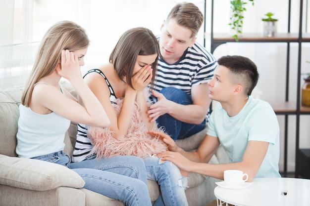 Grupo de amigos tentando apoiar o amigo. jovens acalmando um amigo.