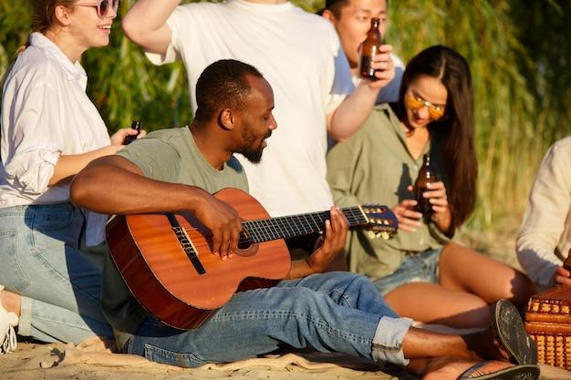 Grupo de amigos tilintando copos de cerveja durante piquenique na praia, estilo de vida, amizade se divertindo