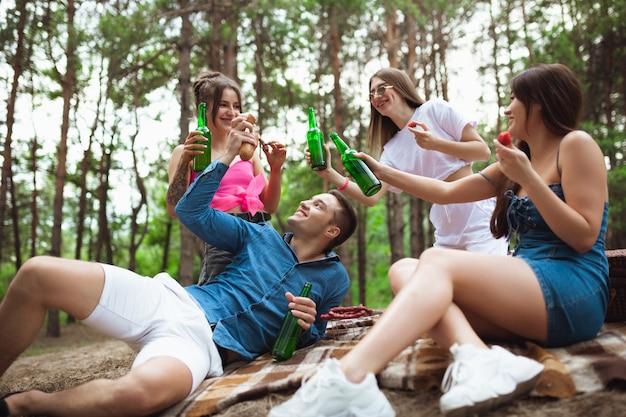 Grupo de amigos tilintando garrafas de cerveja durante um piquenique na amizade de estilo de vida na floresta de verão