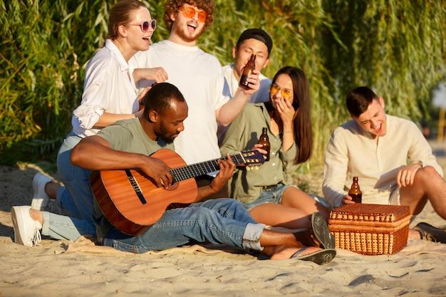 Grupo de amigos tilintando garrafas de cerveja durante um piquenique na praia. estilo de vida, amizade, diversão, fim de semana e conceito de descanso.