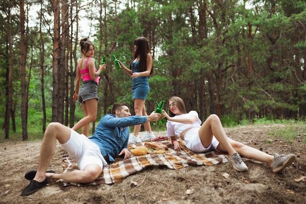 Grupo de amigos, tilintar de garrafas de cerveja durante um piquenique na floresta de verão.