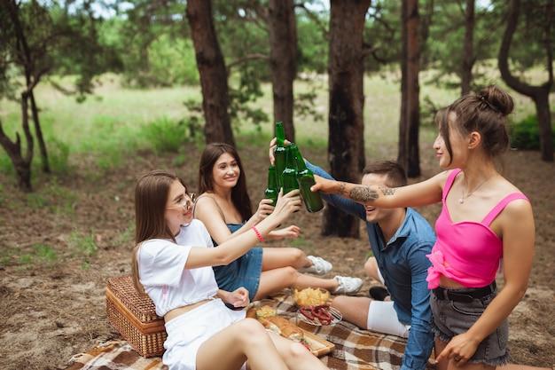 Grupo de amigos, tilintar de garrafas de cerveja durante um piquenique na floresta de verão