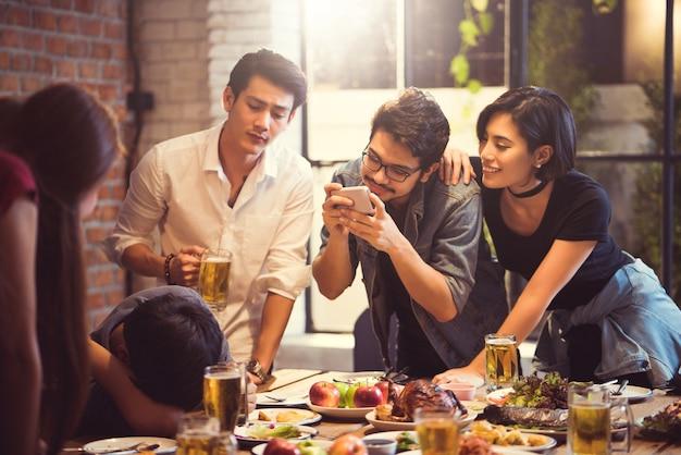 Grupo de amigos tirando fotos pessoas que estão intoxicadas de beber os asiáticos