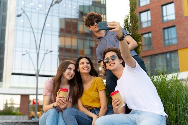 Grupo de amigos tirando selfie ao ar livre enquanto toma um café