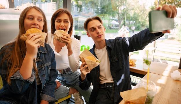Grupo de amigos tirando selfie enquanto comem fast food