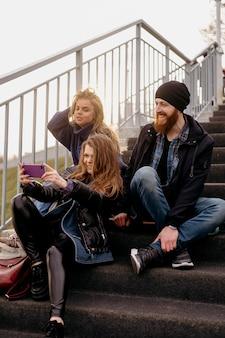 Grupo de amigos tirando selfie na escada