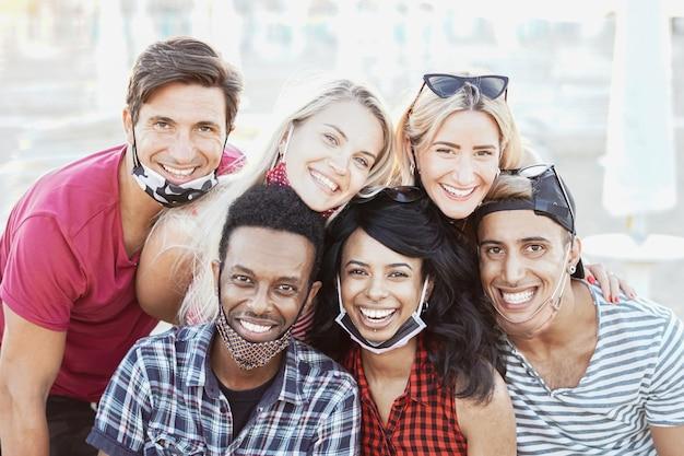 Grupo de amigos tirando uma foto sorrindo com máscara facial