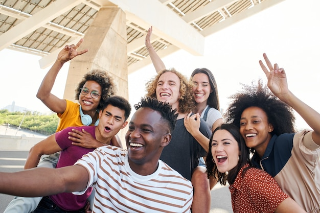 Grupo de amigos tirando uma selfie e se divertindo na cidade, simpáticos jovens inter-raciais