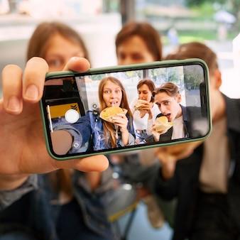 Grupo de amigos tirando uma selfie enquanto comem fast food