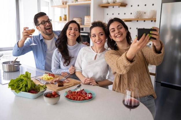 Grupo de amigos tirando uma selfie na cozinha