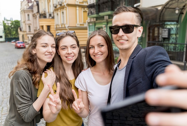 Grupo de amigos tomando selfie ao ar livre