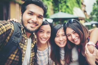 Grupo de amigos tomando selfie em uma rua urbana se divertindo juntos.