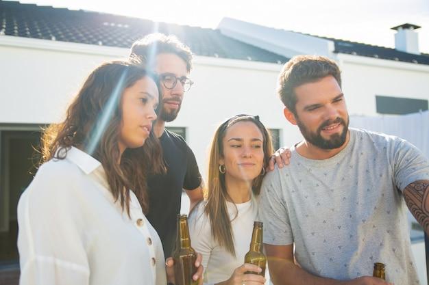 Grupo de amigos tomando selfie enquanto bebia cerveja