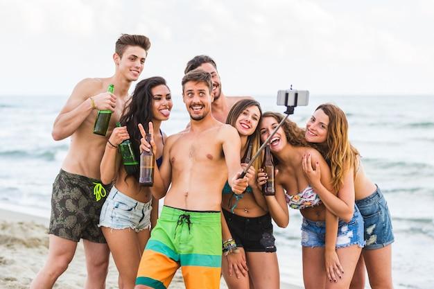 Grupo de amigos tomando selfie na praia