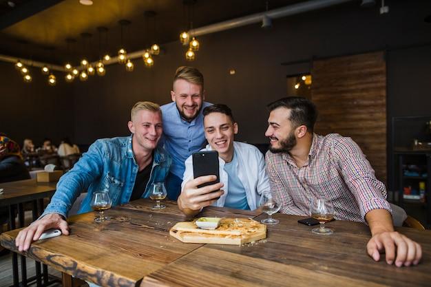 Grupo de amigos tomando selfie no restaurante