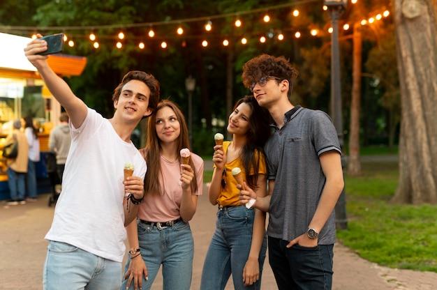 Grupo de amigos tomando sorvete ao ar livre e tirando selfie