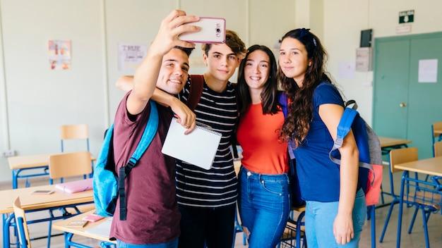 Grupo de amigos tomando um selfie na sala de aula