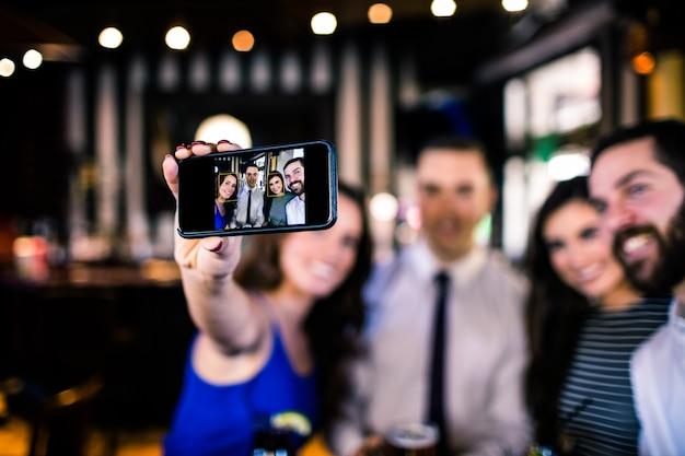 Grupo de amigos tomando uma selfie em um bar