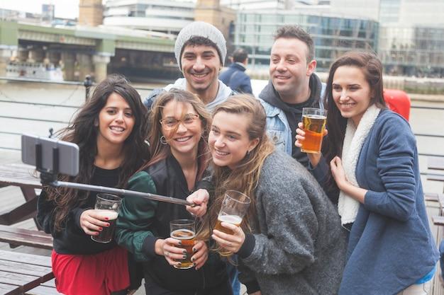 Grupo de amigos tomando uma selfie no pub em londres