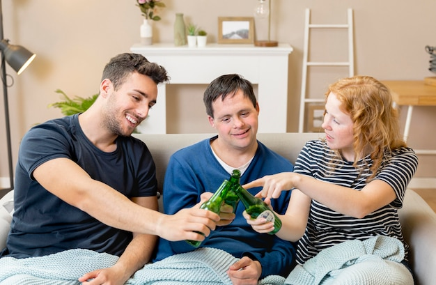 Grupo de amigos torcendo com cerveja em casa