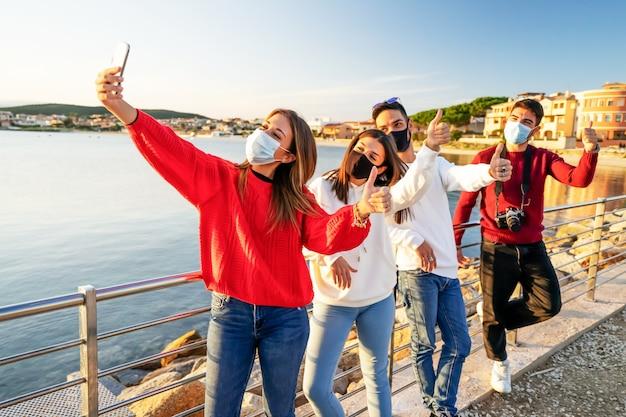 Grupo de amigos usando máscara de proteção facial de coronavirus fazendo uma selfie em fila mostrando os polegares para cima