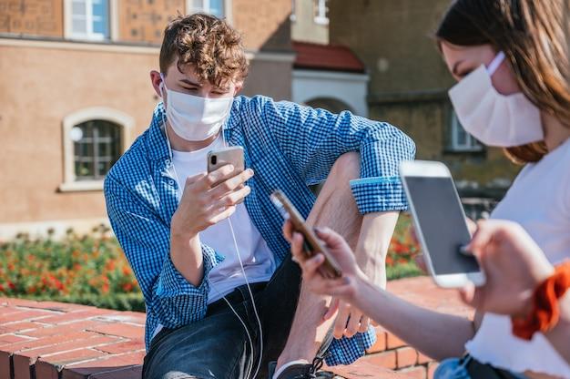 Grupo de amigos usando máscara facial e usando seus smartphones