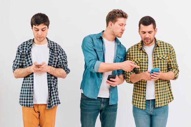 Grupo de amigos usando telefone celular contra o pano de fundo branco