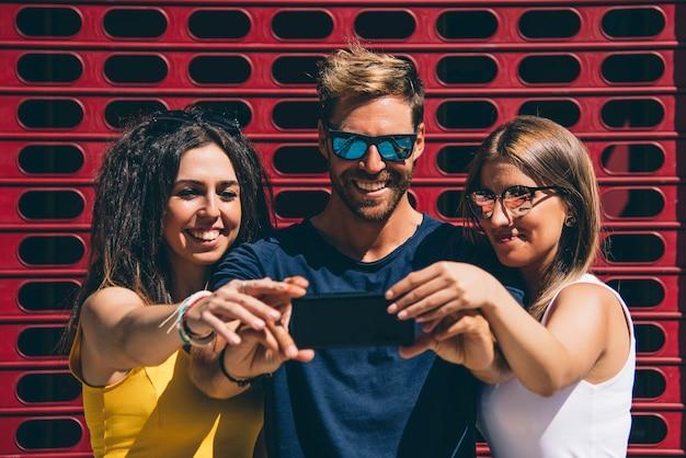 Grupo de amigos usando telefone móvel esperto - conceito de dependência.