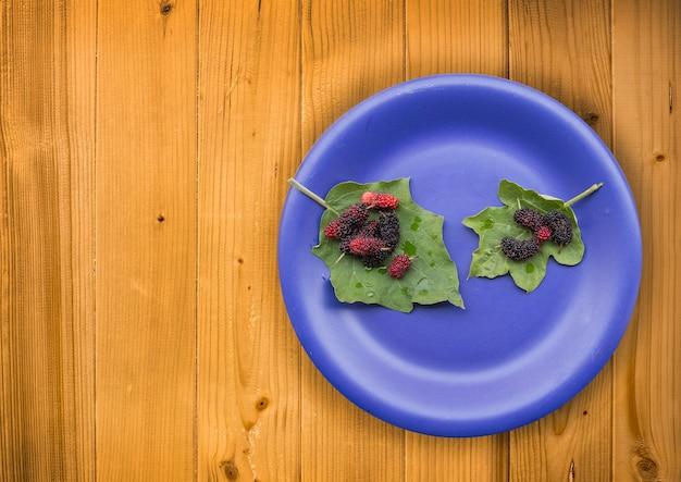 Grupo de amoras na folha com prato azul na mesa de madeira