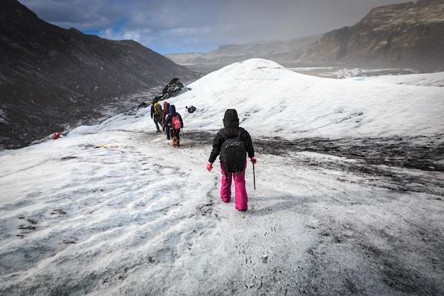 Grupo de andar de pedestrianismo na geleira durante a queda de neve pesada em solheimajokull