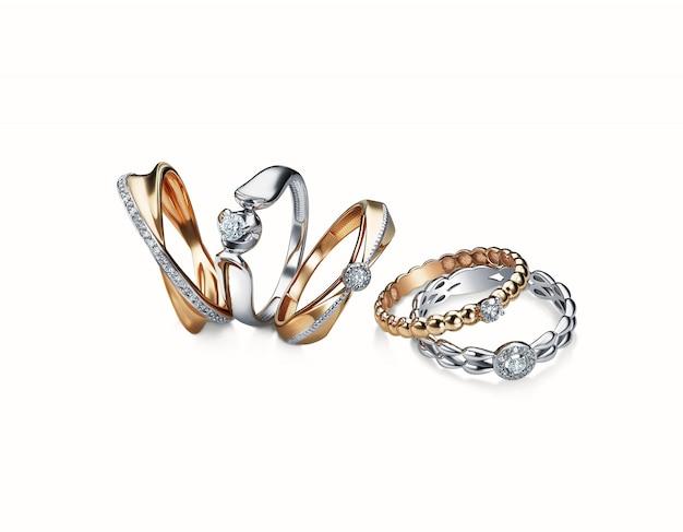 Grupo de aneis de diamante empilhados isolados no fundo branco, ouro branco, ouro amarelo, trajeto de grampeamento incluído. extremo close-up.