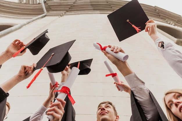 Grupo de ângulo baixo de estudantes com diploma