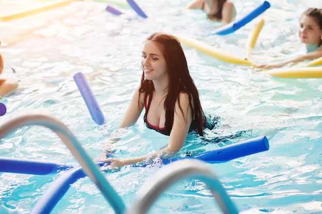 Grupo de aptidão de meninas fazendo exercícios aeróbicos na piscina no parque aquático.